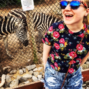 blond girl at zoo with zebras