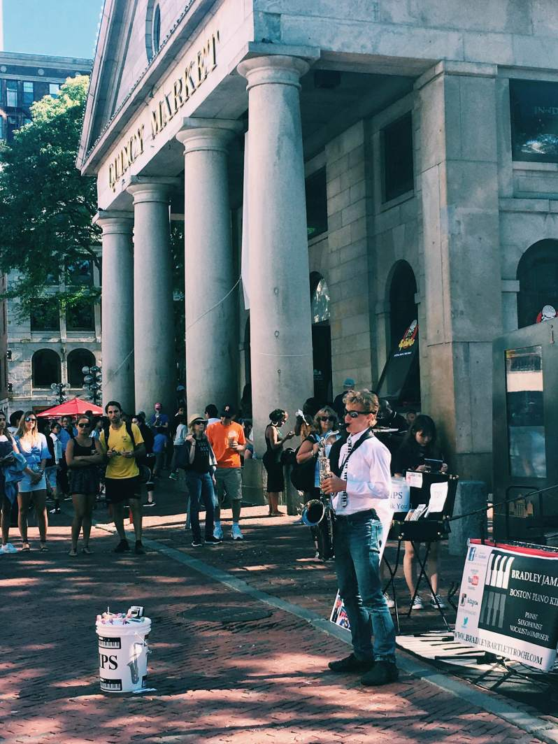saxophone street performer in crowd by quincy market boston